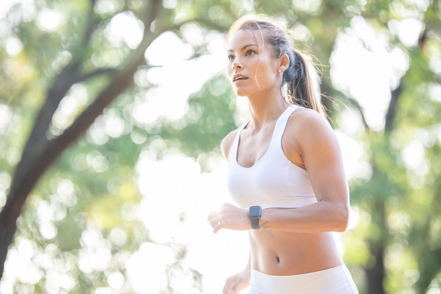 Woman trail running on wooded trail in white sportswear by health and fitness photographer Robert Houser
