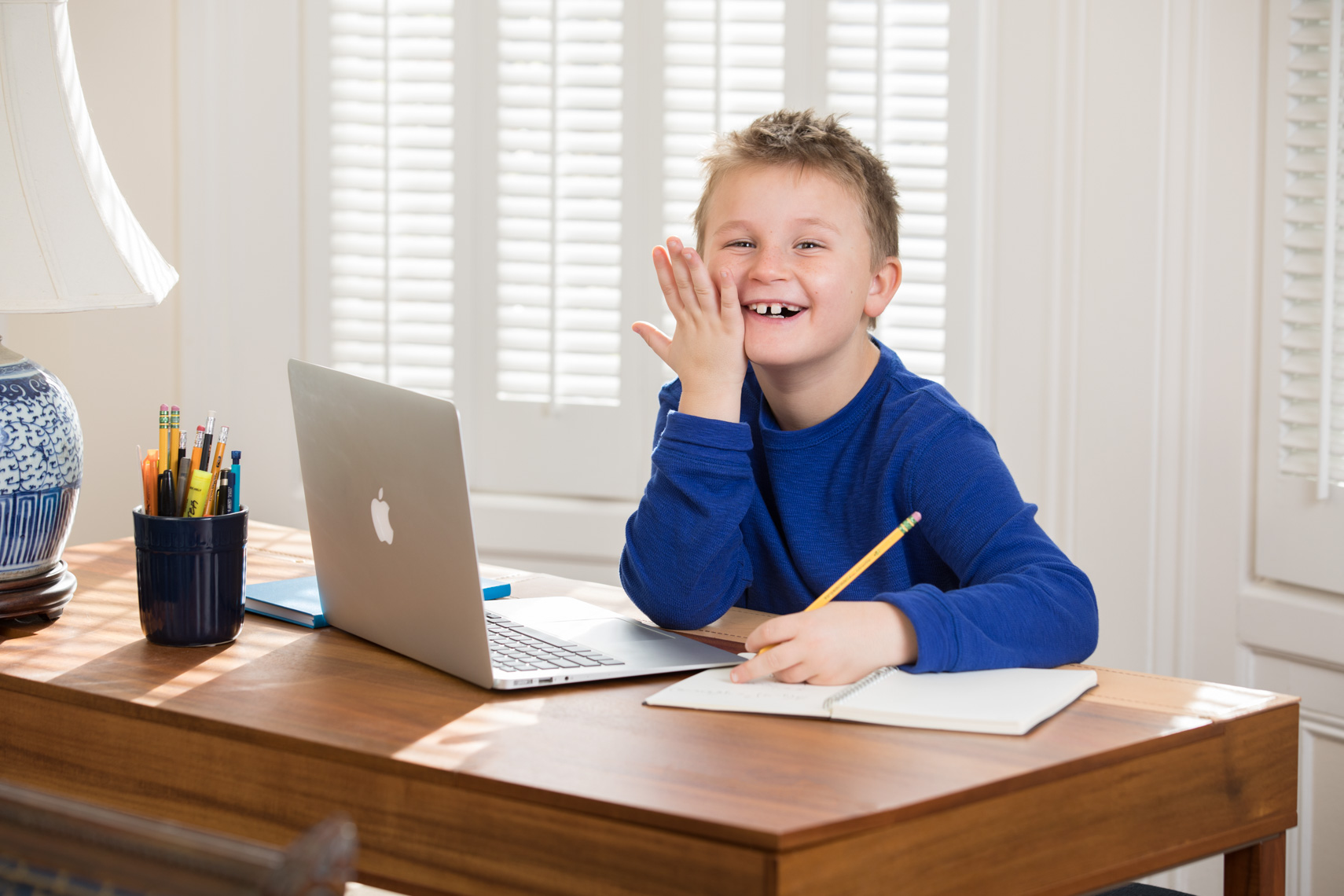 Portrait of a young boy doing homework at a deskwith a laptop