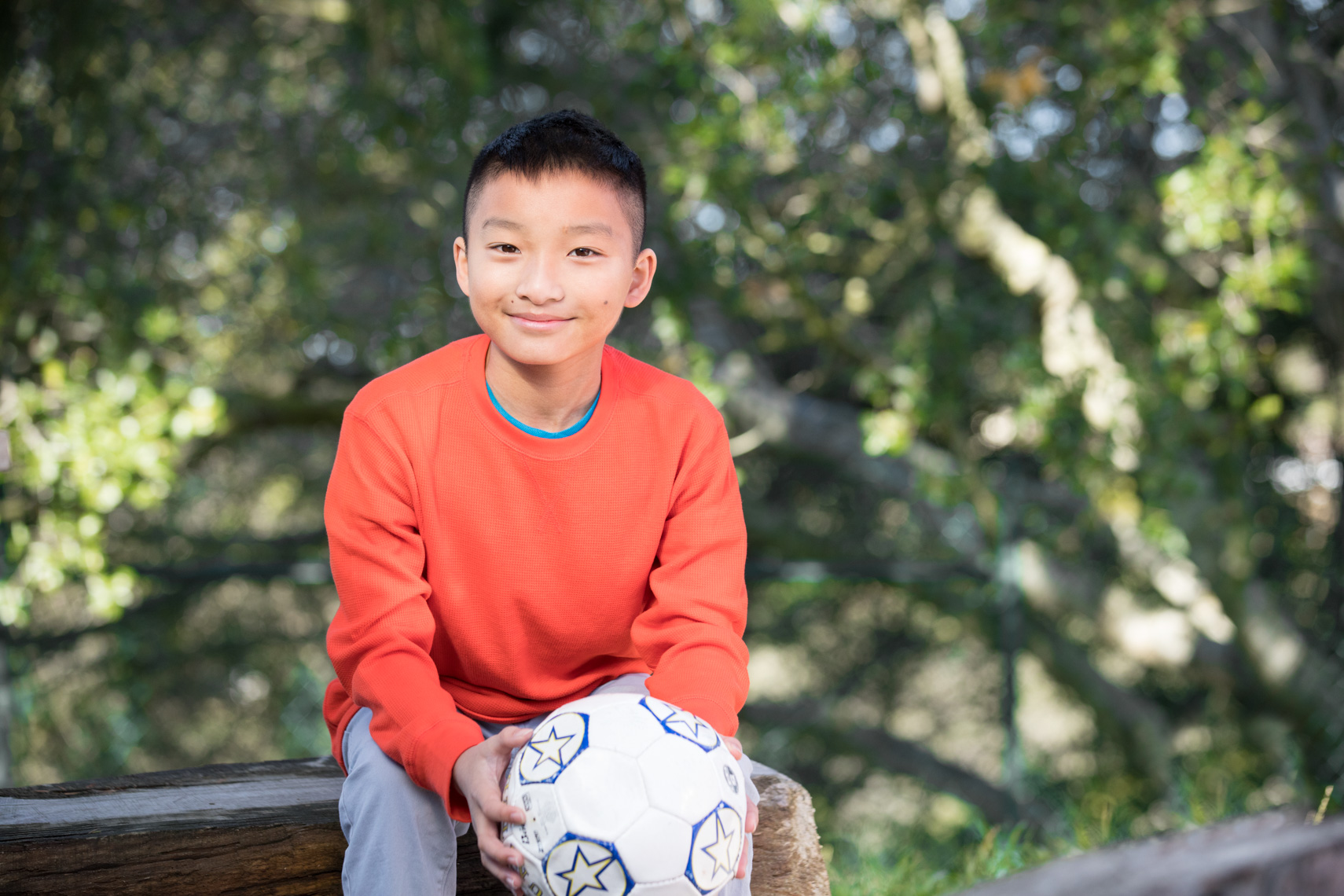 Portrait of a young boy outside holding a soccer ball