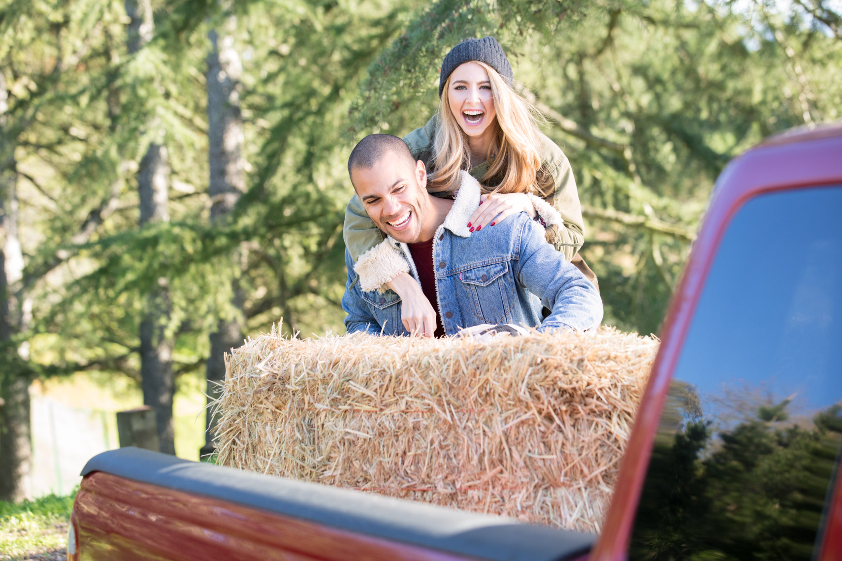 Young couple unloads hay out of the back of a pickup truck