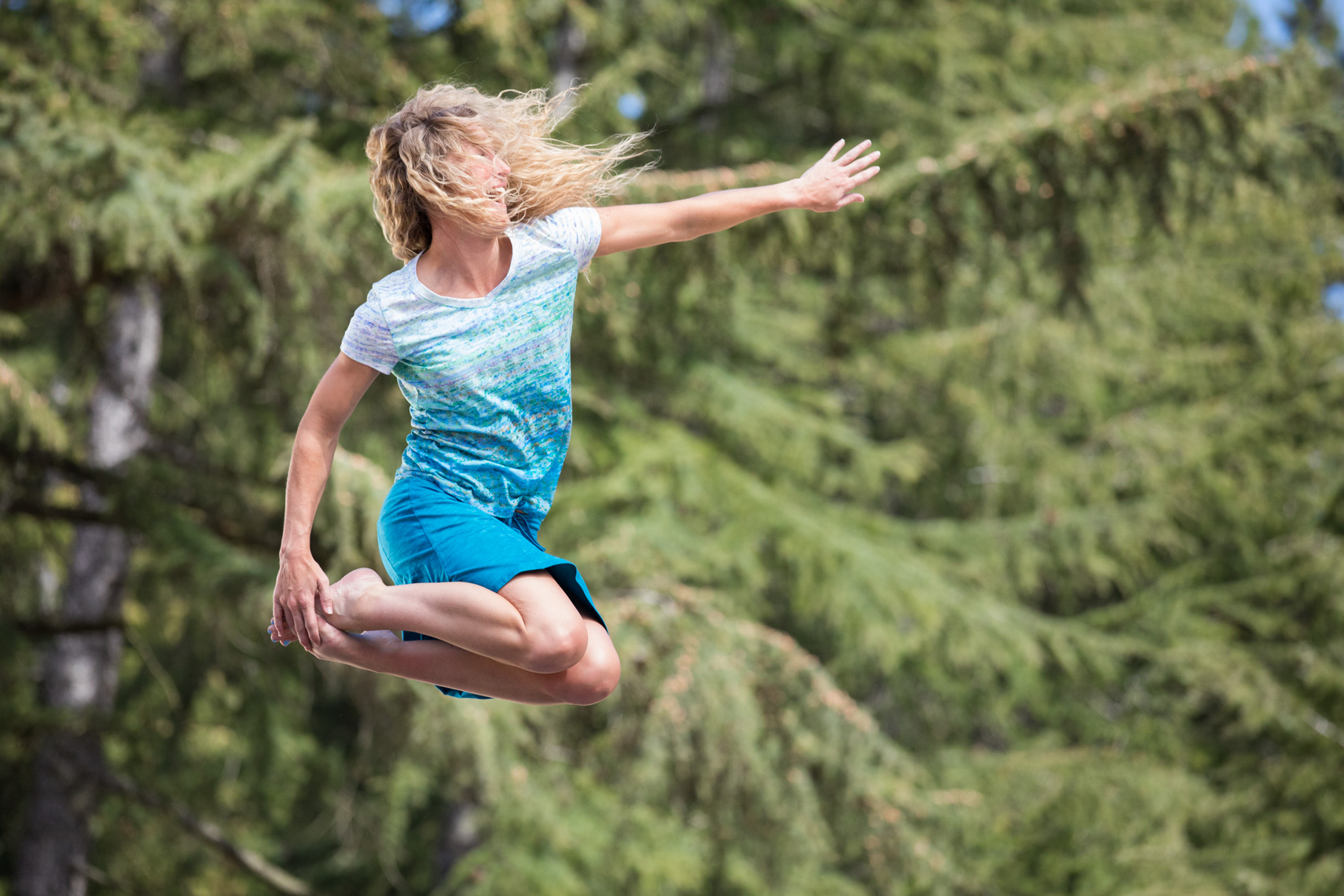 Woman leaping in the air and grabbing her toes