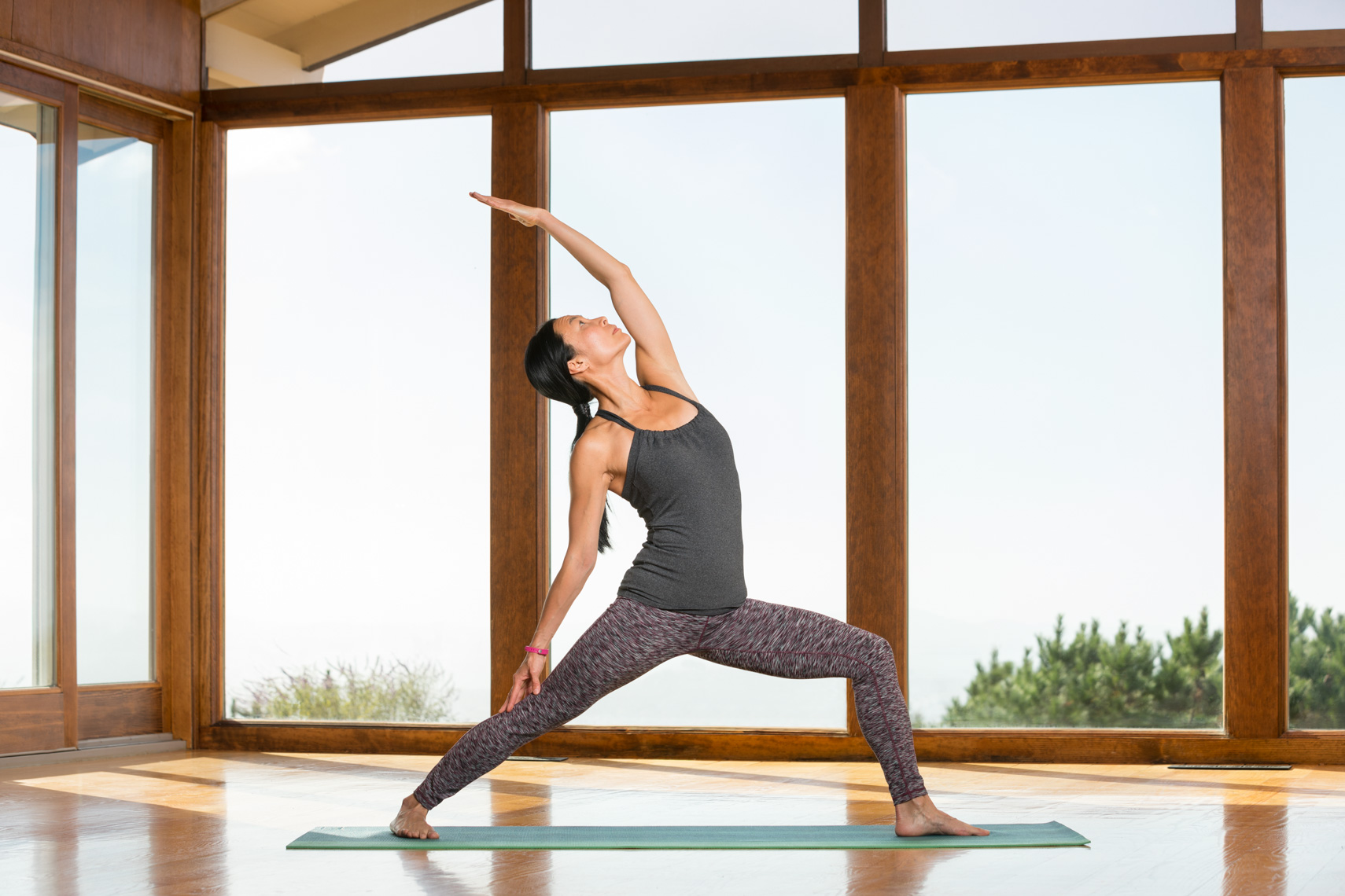 Woman stretches and does yoga in indoor yoga studio